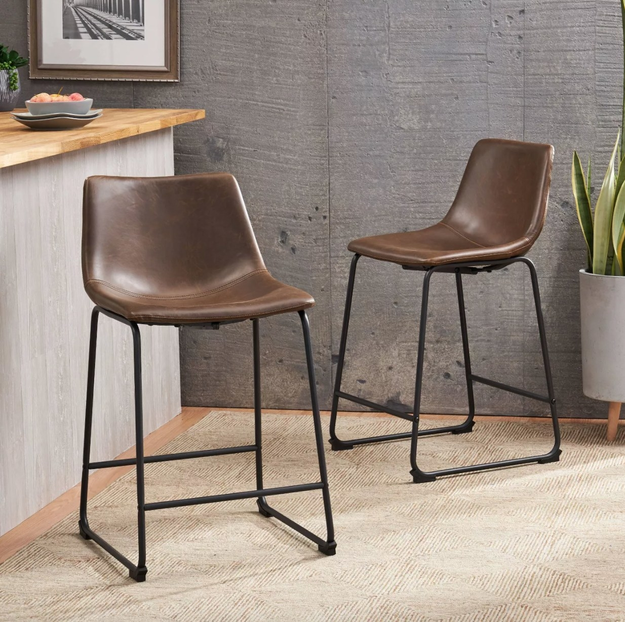 Two brown faux leather bar stools with metal legs