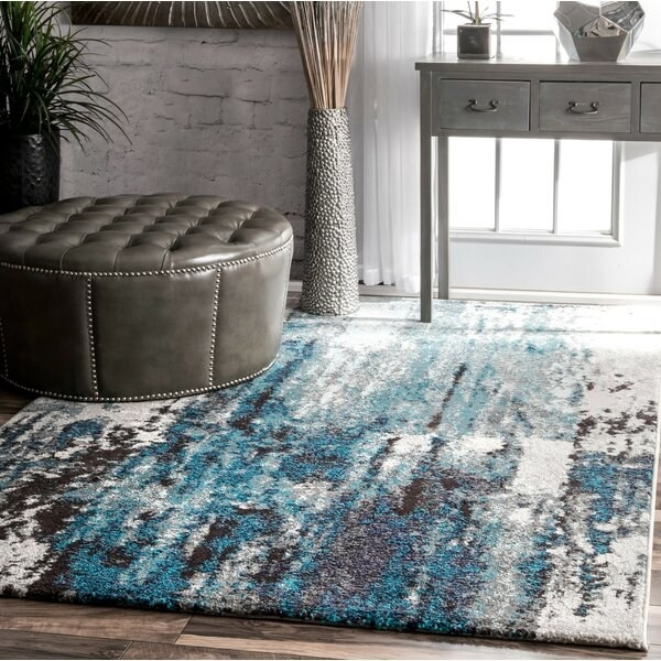 The rug, which has a blue, white, gray and black abstract pattern
