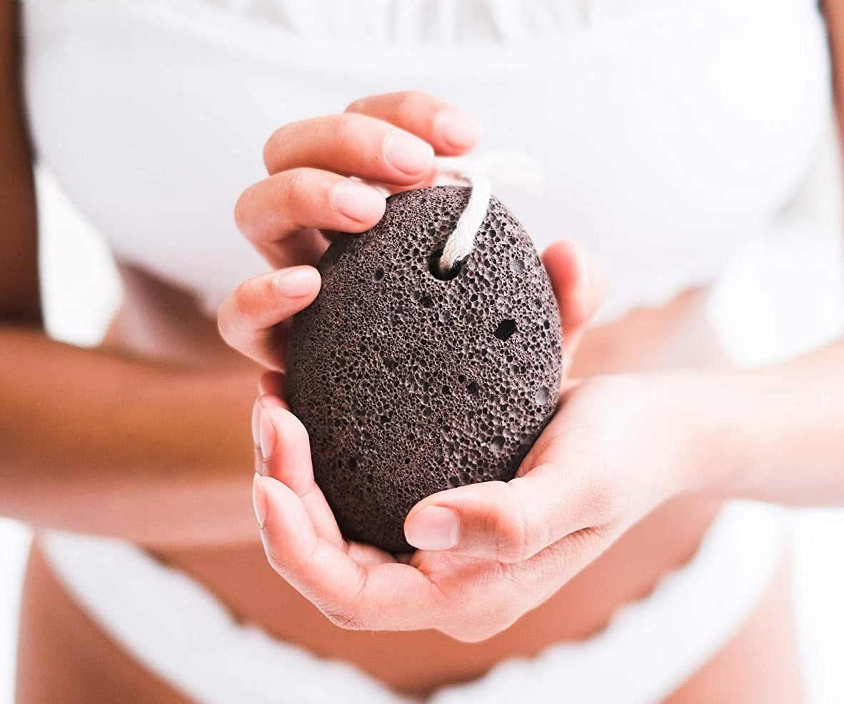 A person holding the pumice stone