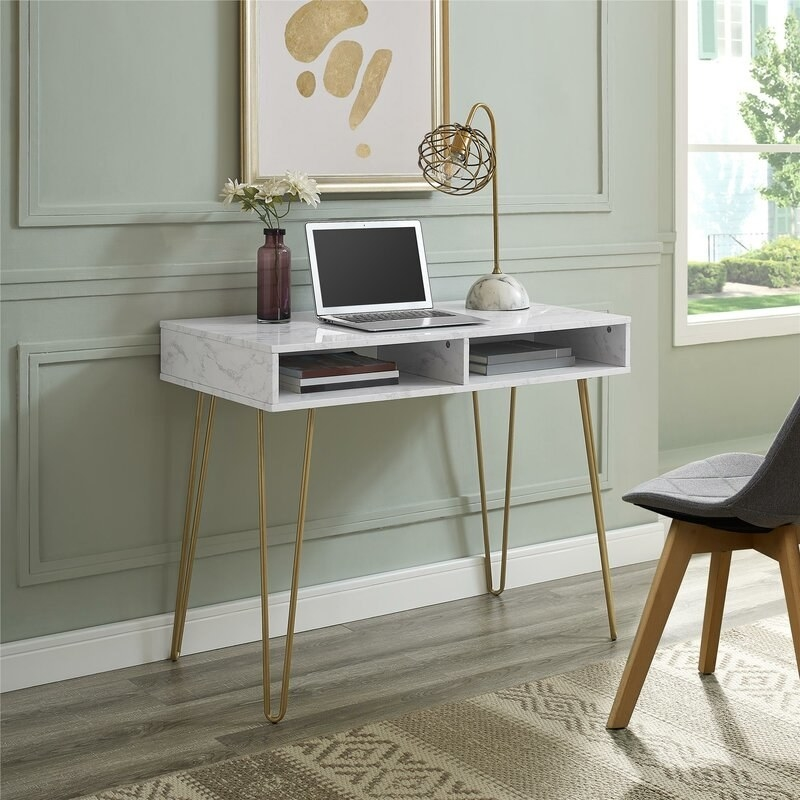 The desk, which has a white marble print and gold hairpin legs, and two open cubbies under the main desktop surface