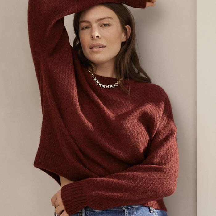 a model wearing the oversized crewneck sweater in burgundy color