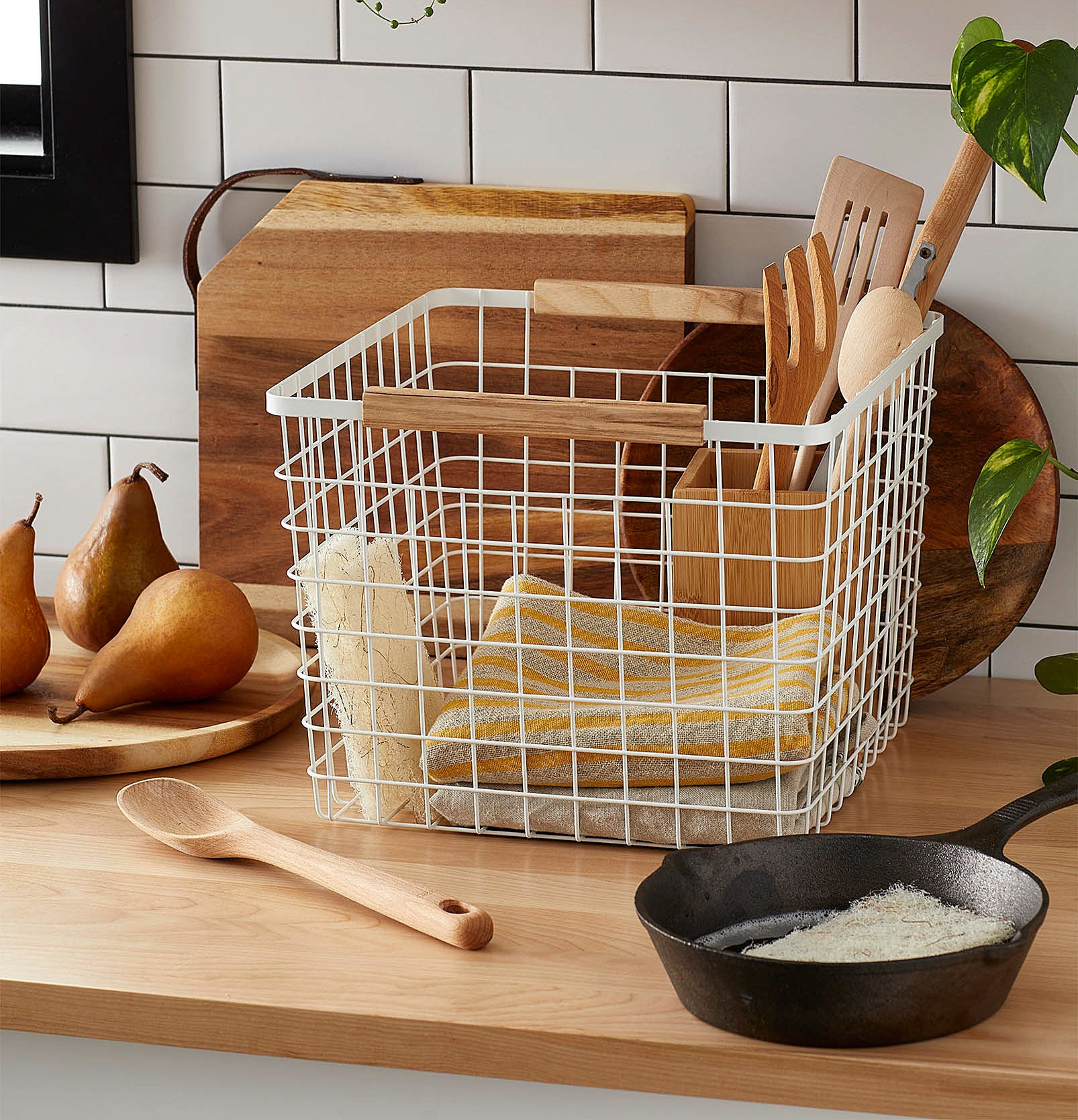A wire basket on a countertop with dish cloths inside