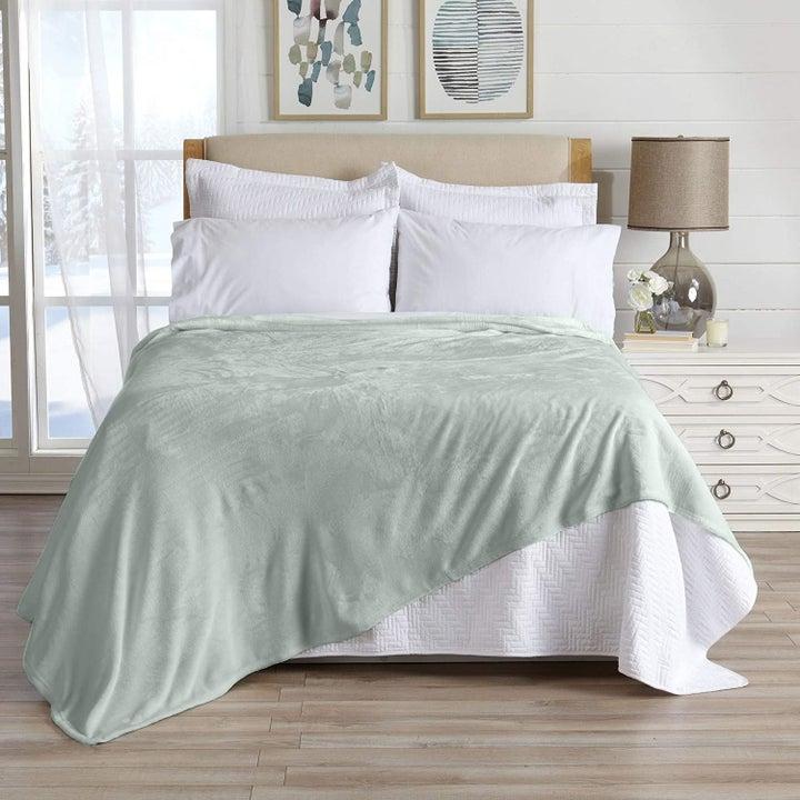Sage green blanket on bed