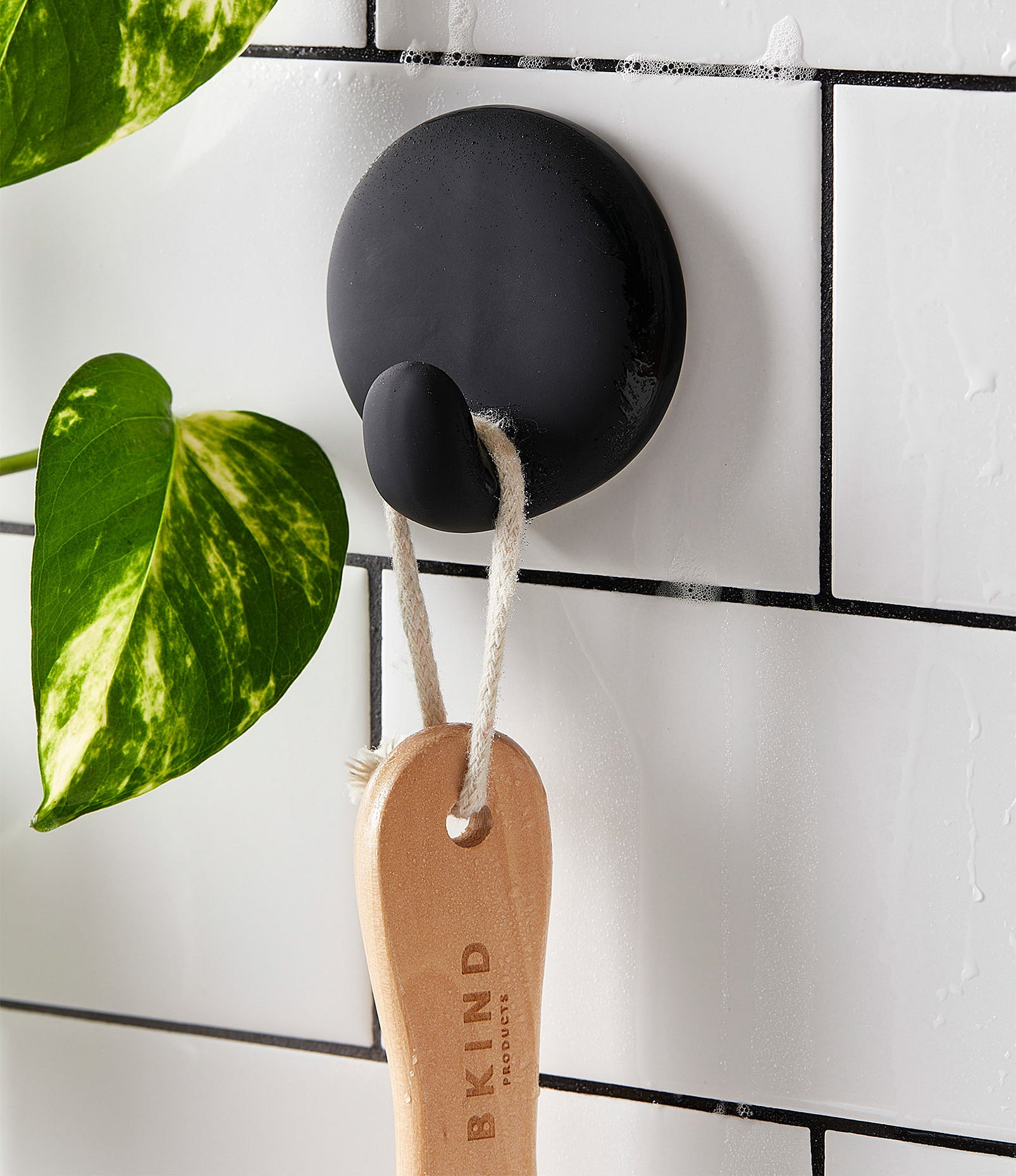 A small hook attached to a tiled wall with a wooden brush hanging from it