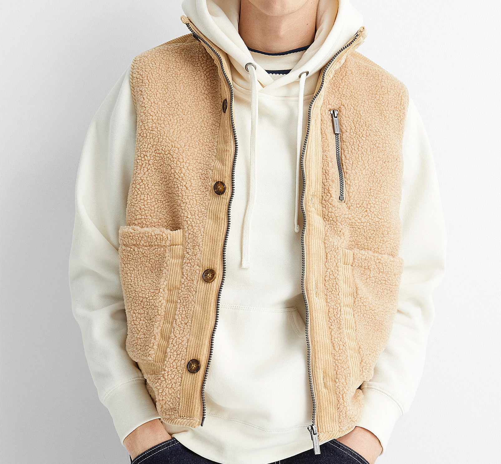 A person wearing the zip-up sherpa vest over a hoodie