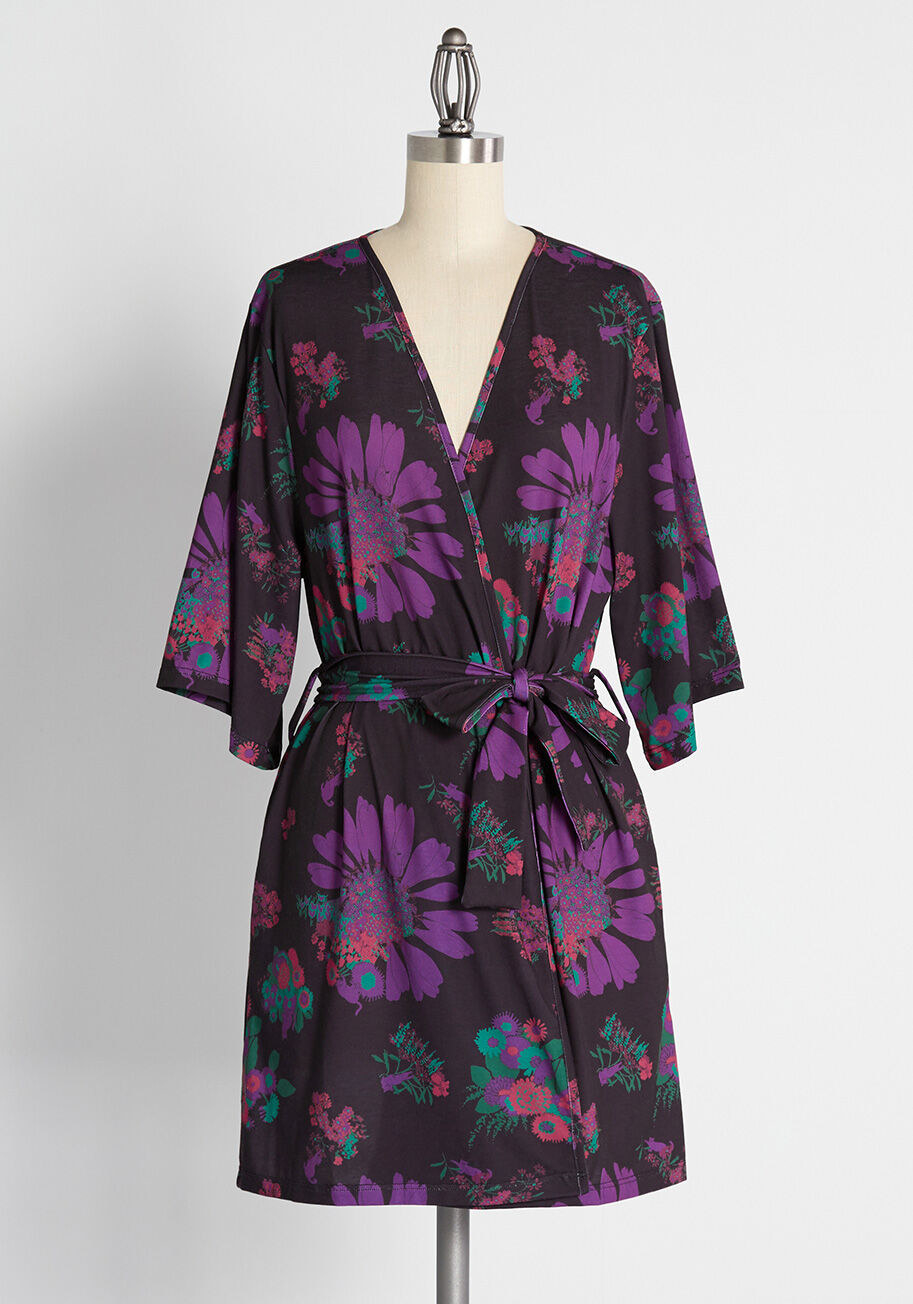 short-sleeved black robe with purple, green, and pink floral pattern all over it