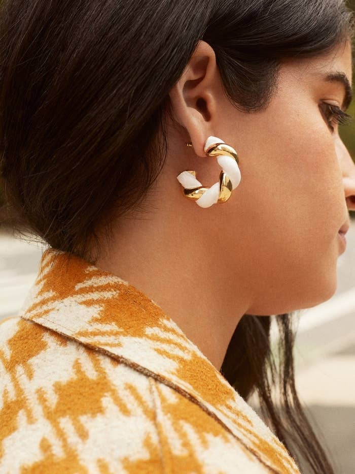 model wearing the  gold and white chunky twist hoops