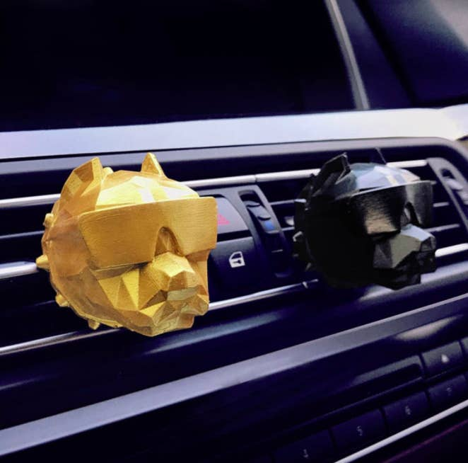 A pair of 3D printed dog head diffusers clipped to car vents
