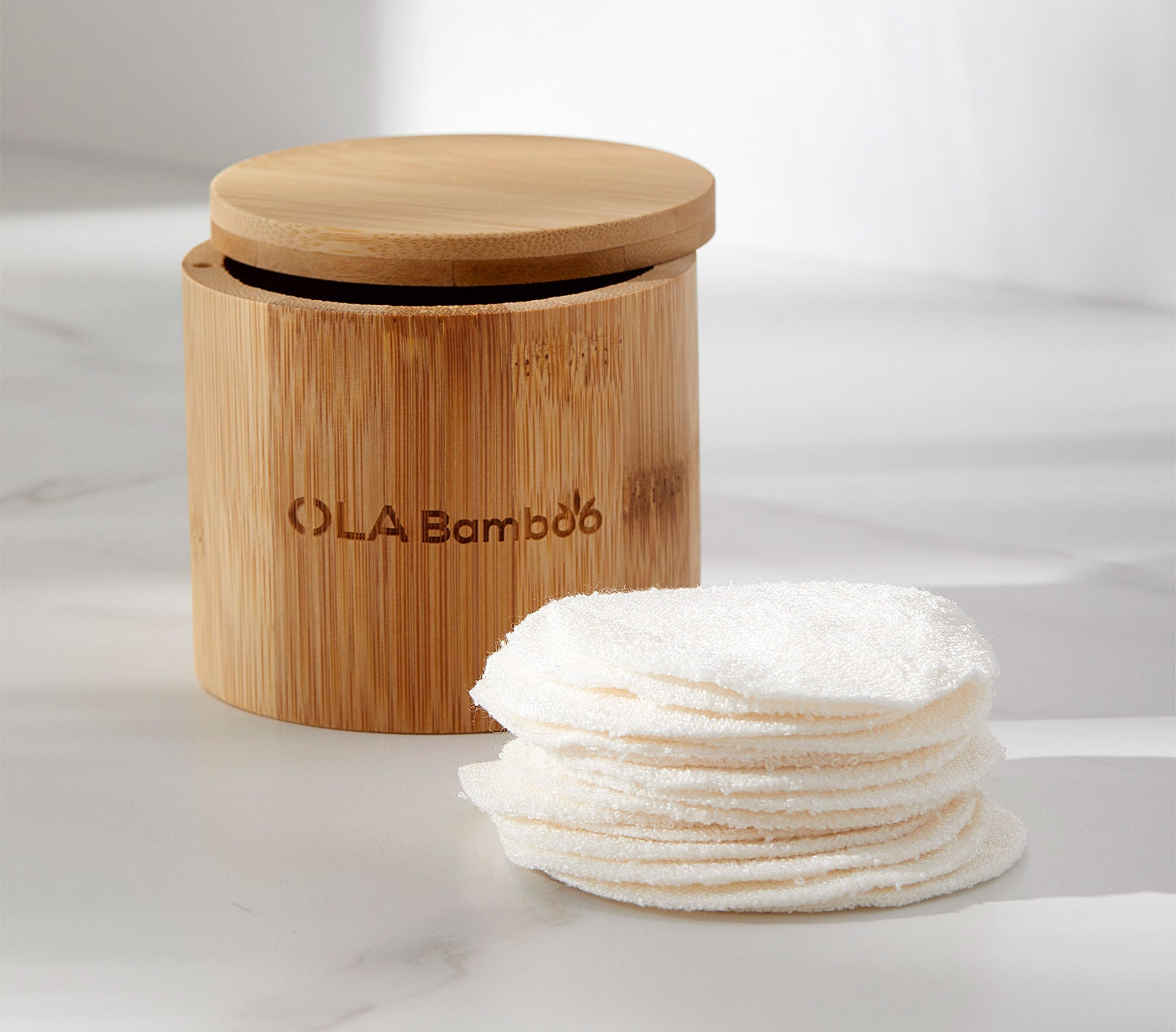 A stack of reusable beauty pads next to the cylinder bamboo container