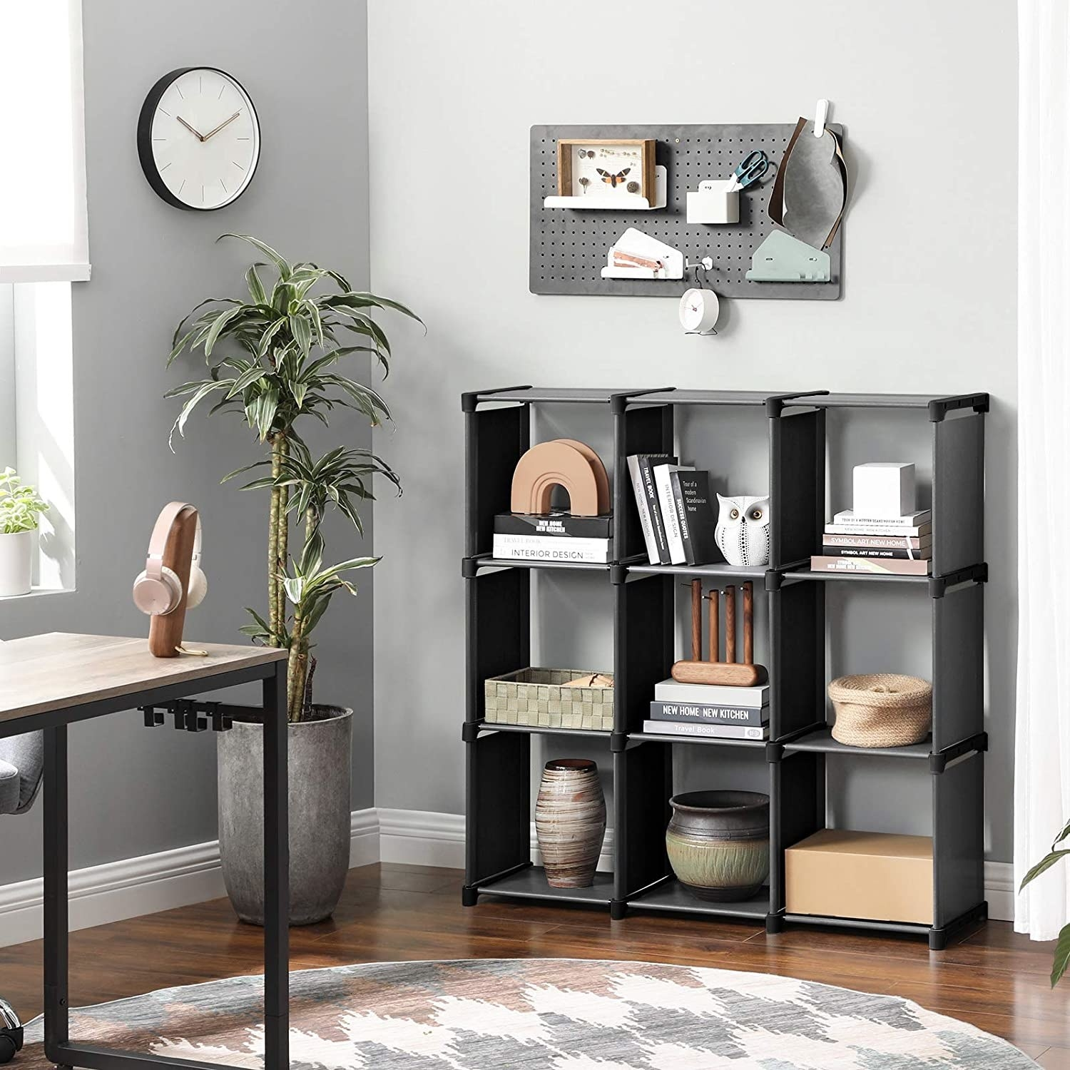 A bookshelf with nine square compartments that are filled with vases, bins, and stacks of books