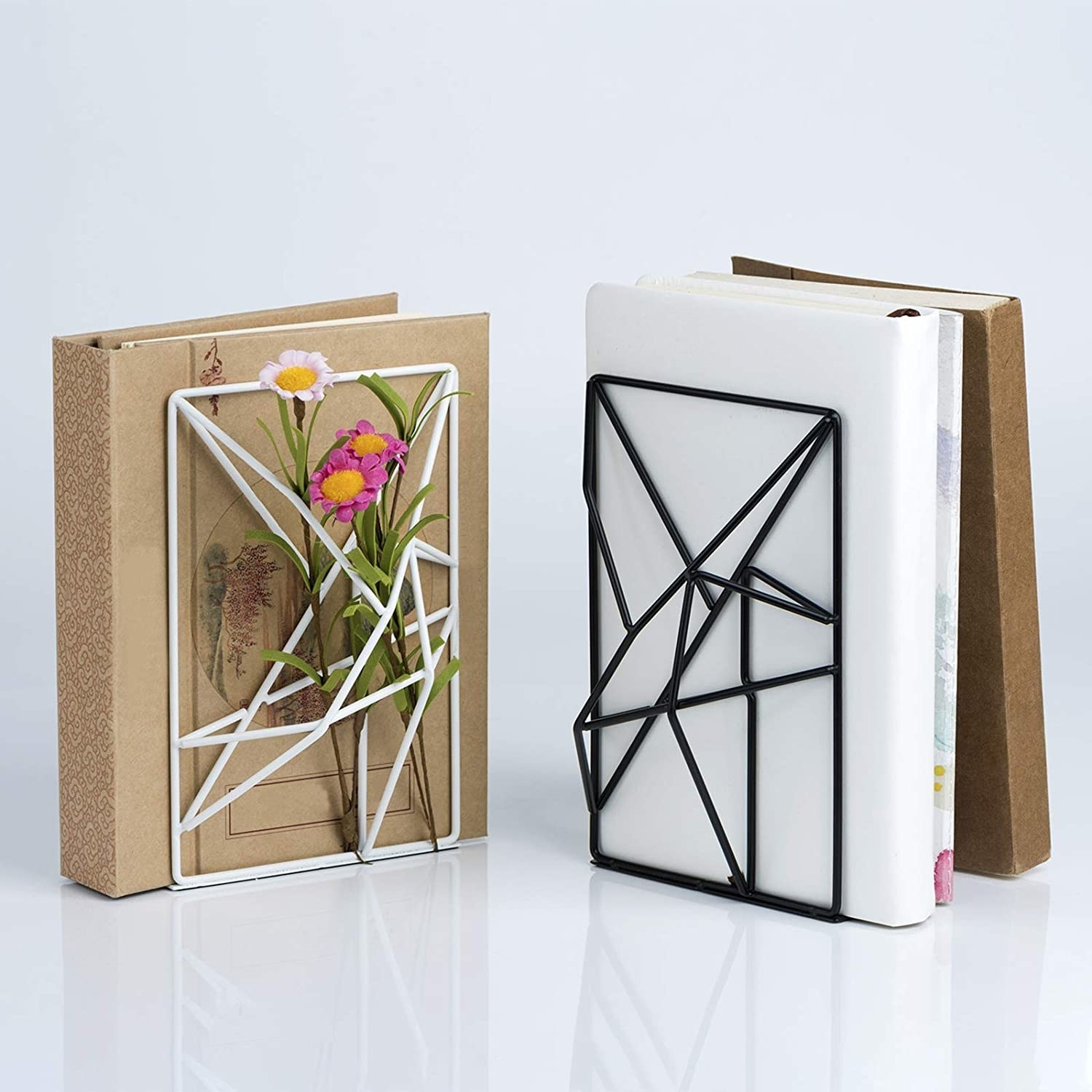 Two wiry metal bookends with books placed beside them
