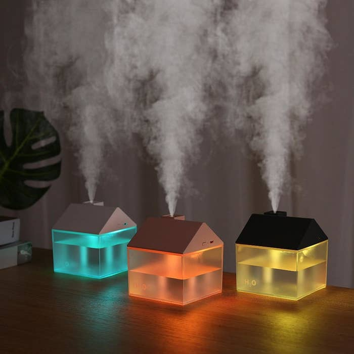 three house-shaped humidifiers with steam escaping from the house chimney