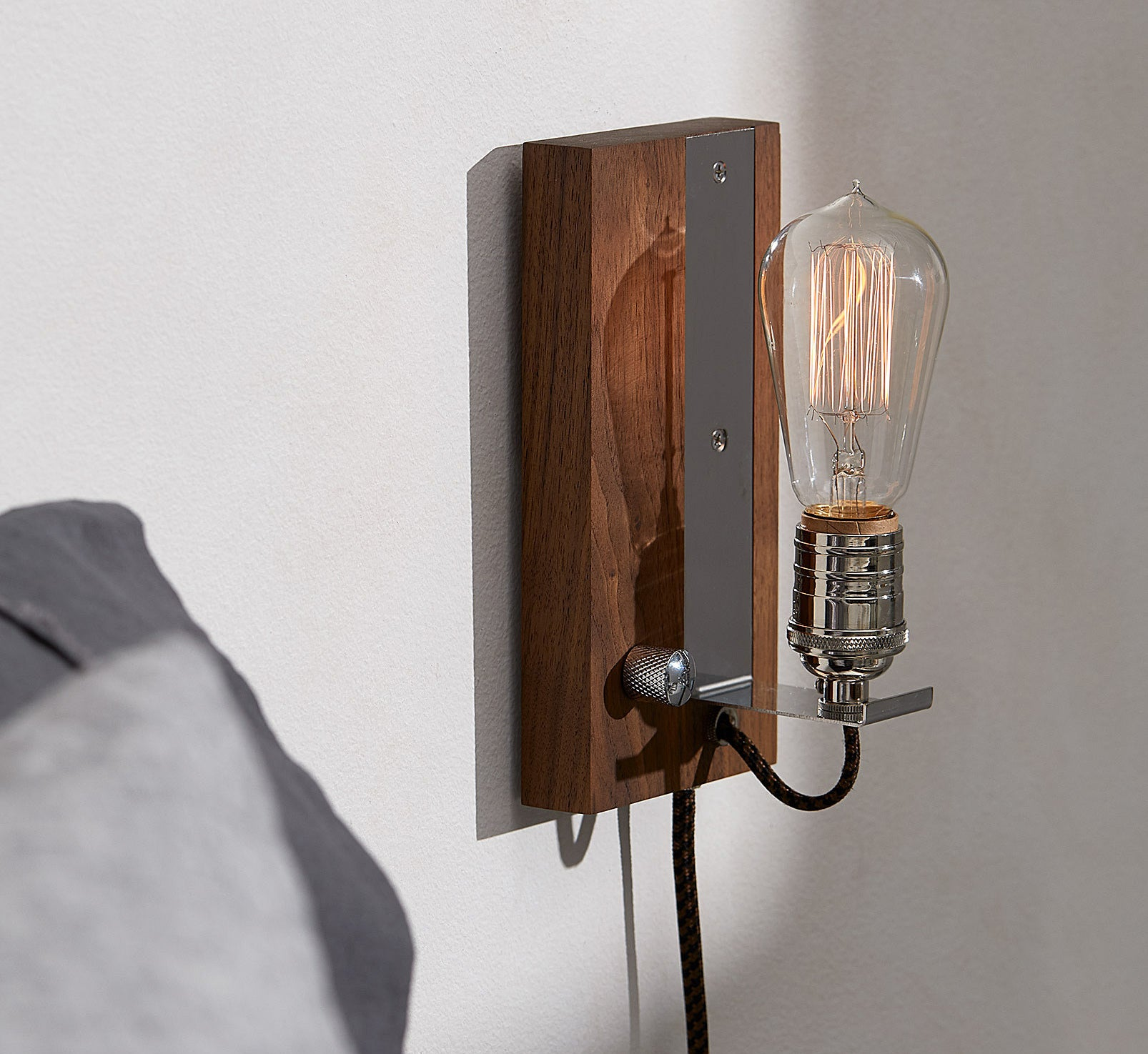 The vintage sconce mounted on a wall with the Edison bulb dimmed down