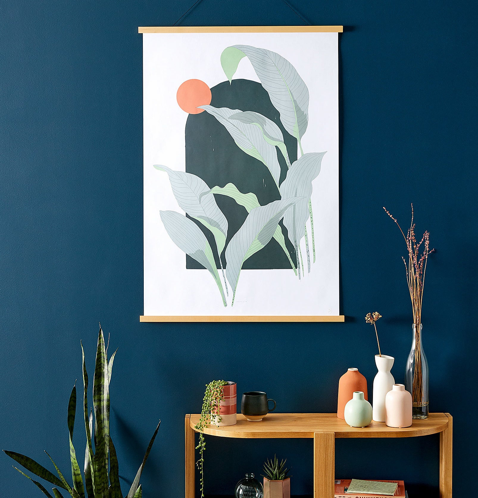 A leafy art print hanging in a frame next to a snake plant and a side table with vases on it