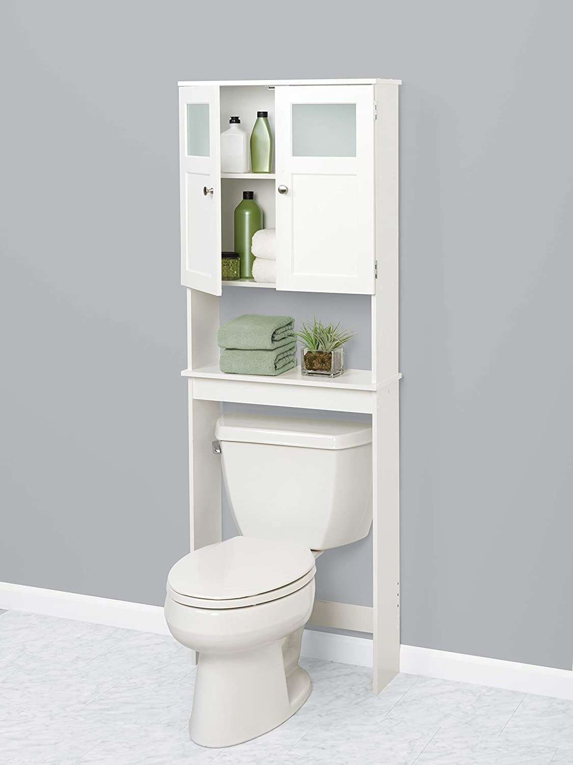 A cabinet with shelves that goes over the toilet