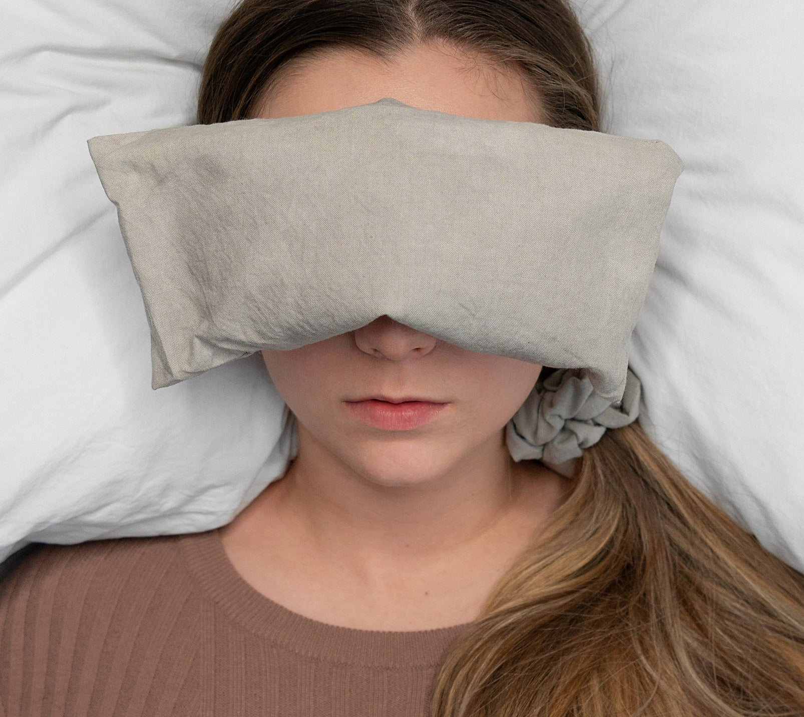 A person lying down with the eye cushion over their eyes