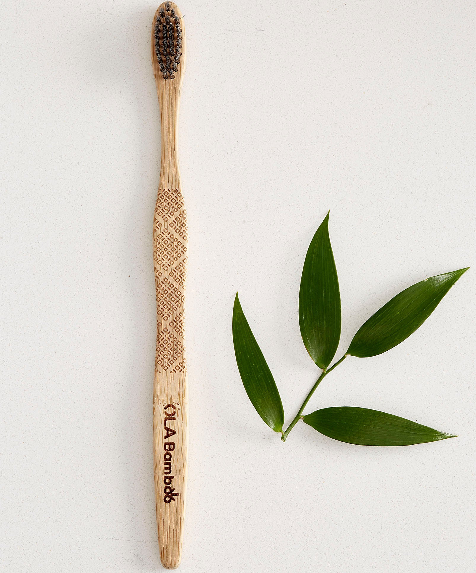 A bamboo toothbrush next to a sprig of leaves