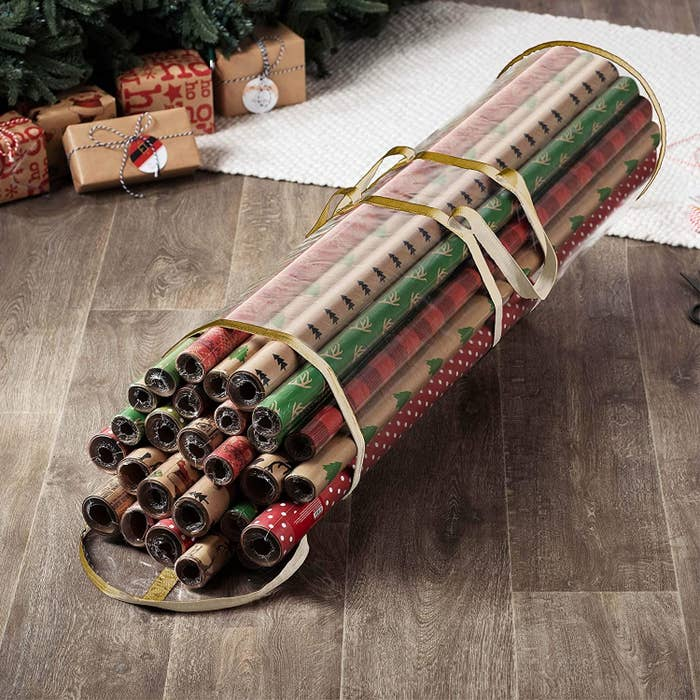 A large plastic bag on the floor with rolls of wrapping paper inside