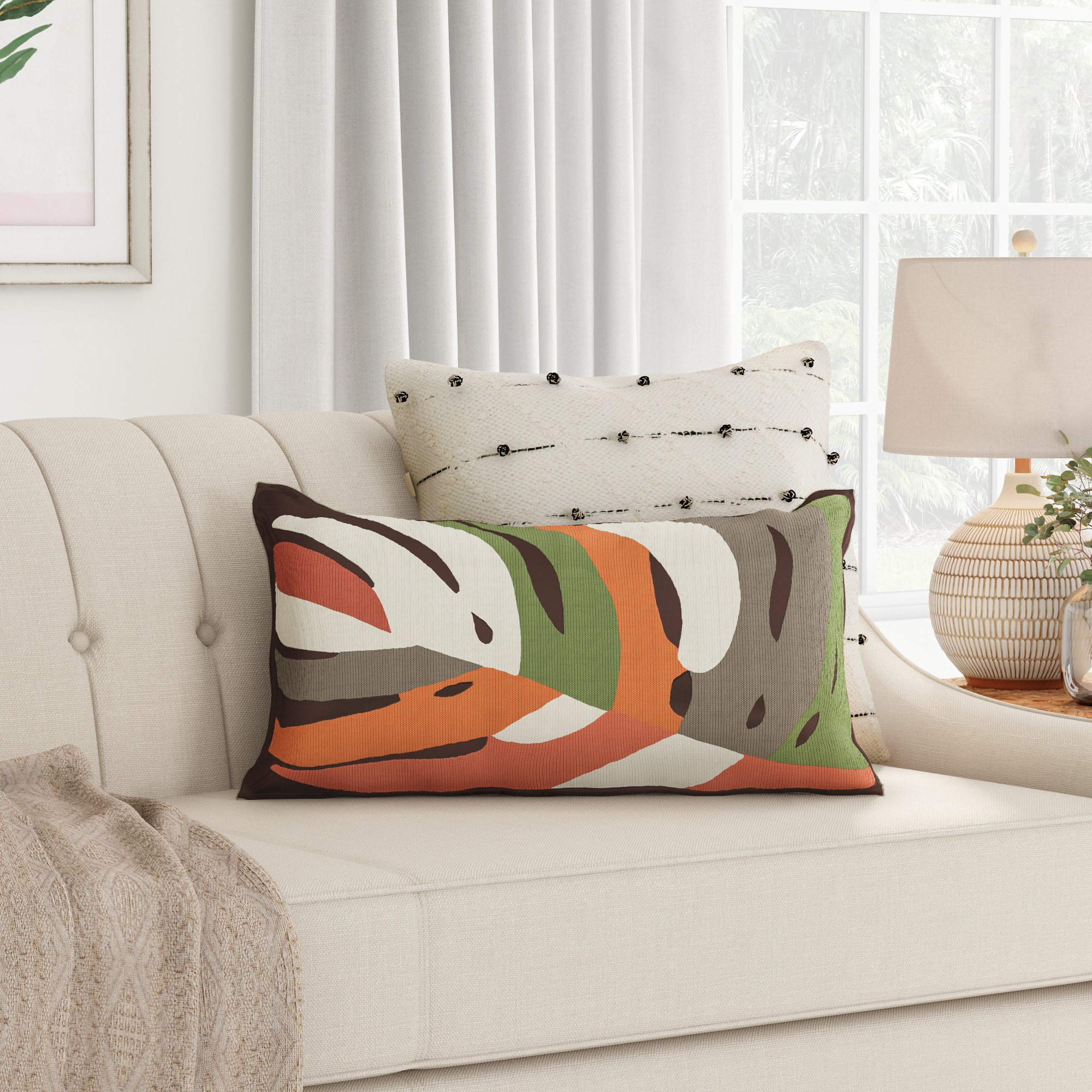 The multicolored leaf-patterned pillow on a couch