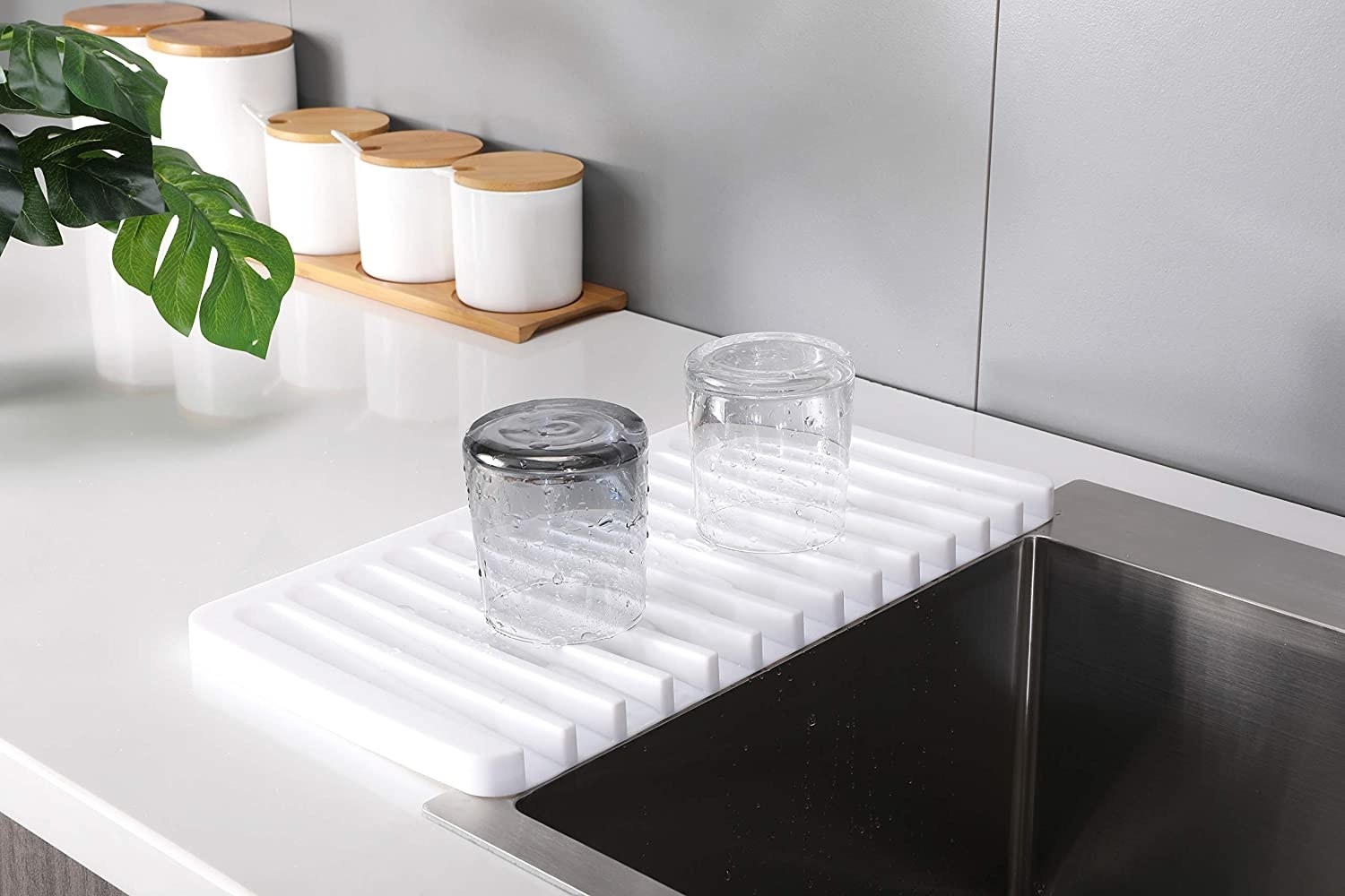 A silicone drainage mat next to a sink with two wet glasses on top