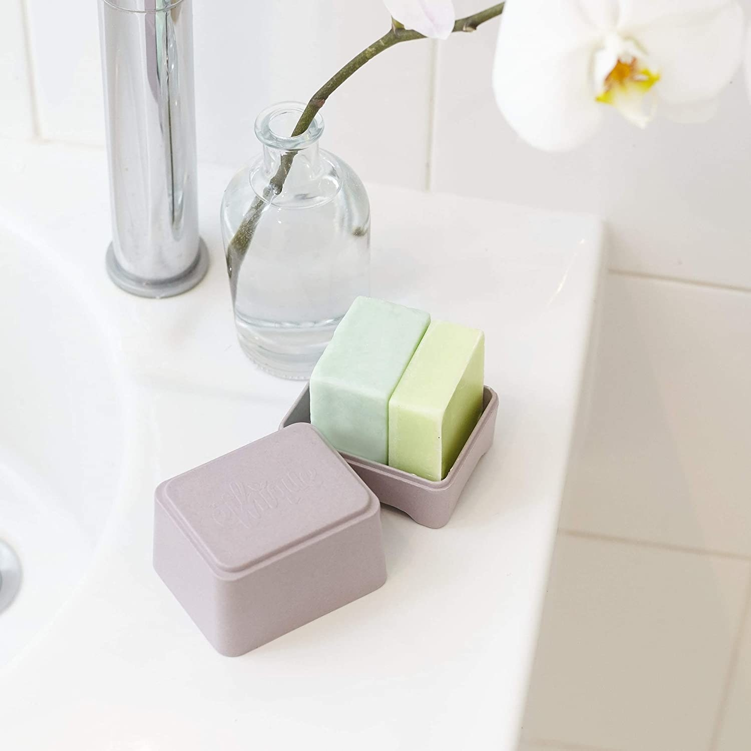 A box containing two soap bars perched on the edge of a tub