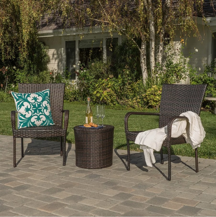 Two brown wicker outdoor patio chairs with brown wicker table