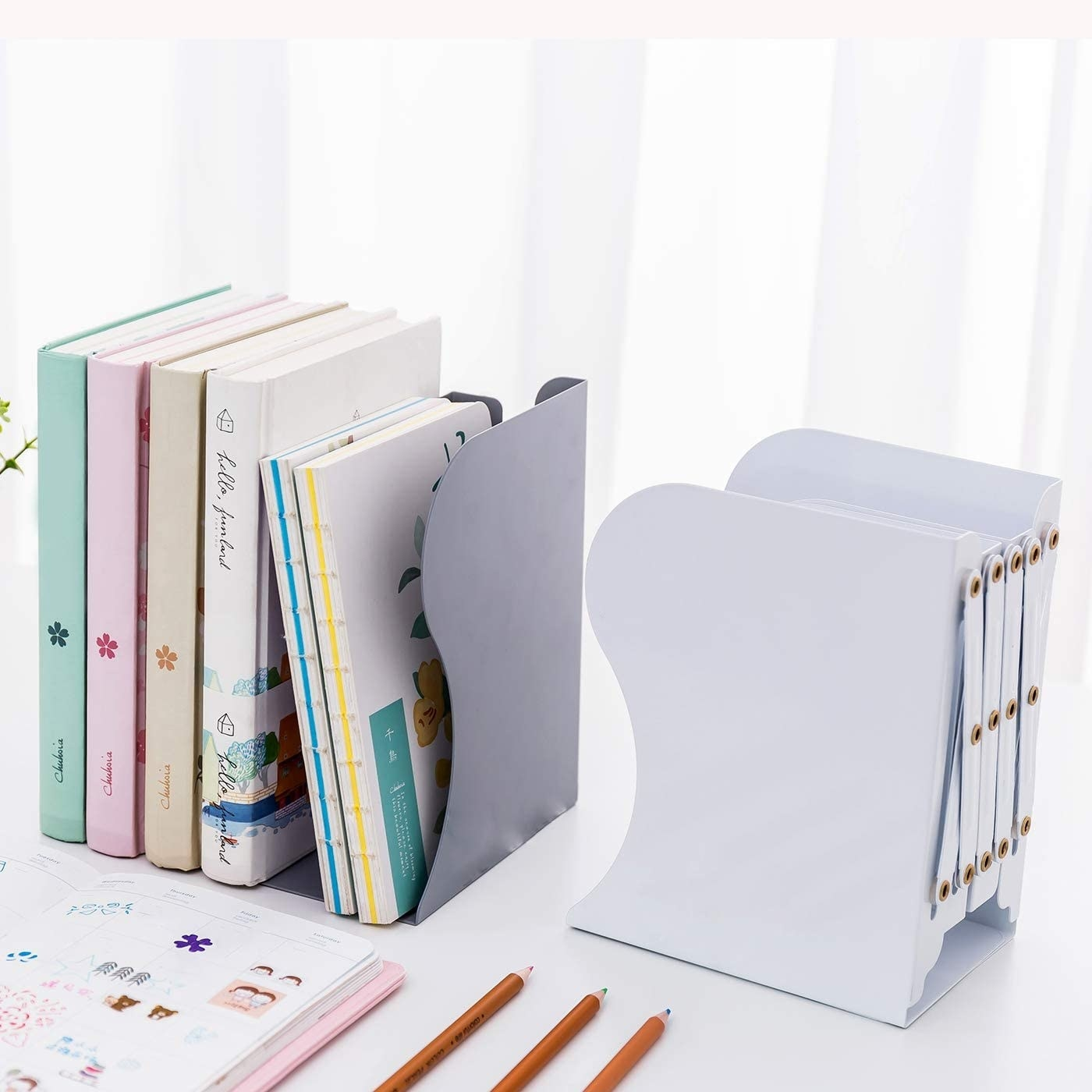 A set of extendable bookends stocked with cookbooks and journals