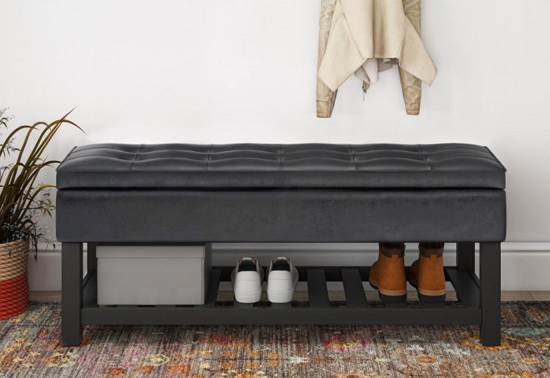 a black leather storage bench with a shelf underneath for shoes
