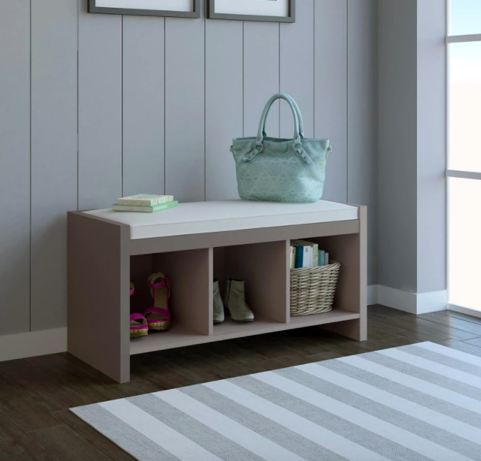 mudroom area with bench that has a cushion on top and three cubbies for storage below