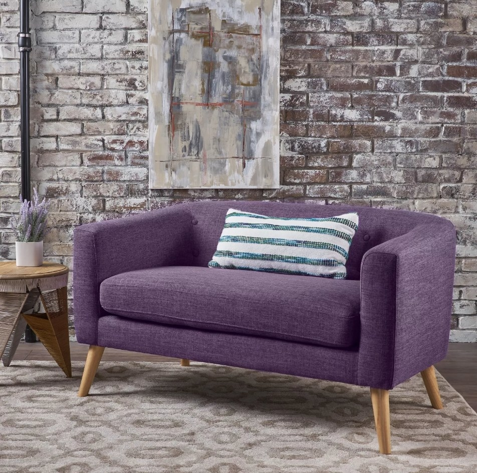 Purple love seat with wooden legs