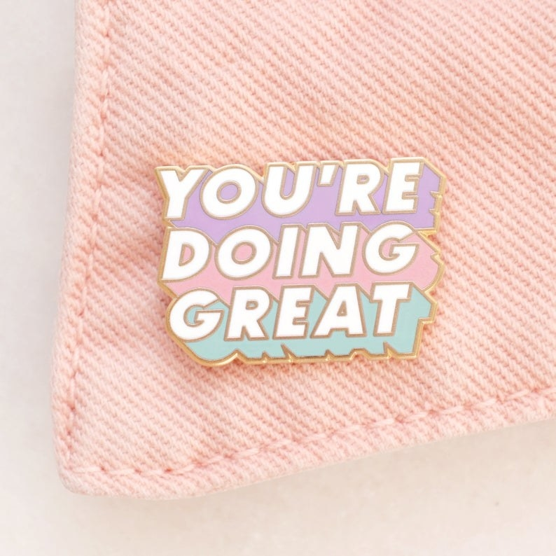 """Pastel green, pink, and lavender pin with white block letters reading """"You're doing great"""""""