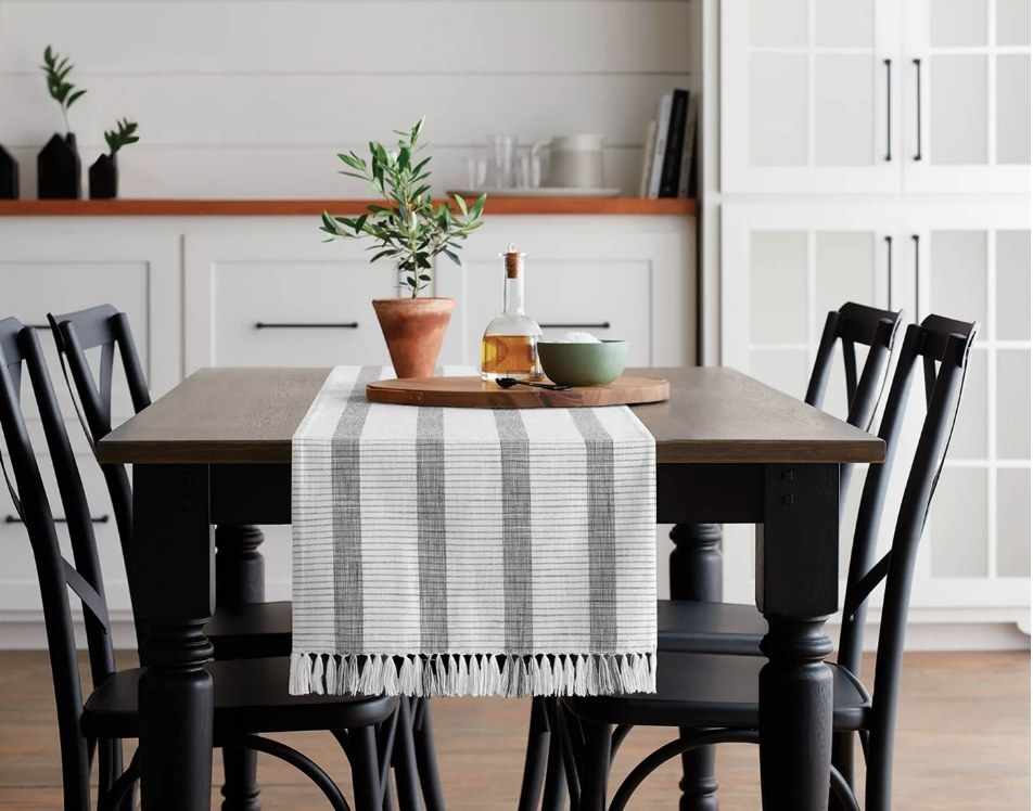 White and gray striped table runner with fringe detailing