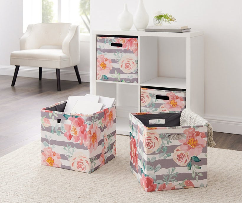 the two bins with gray and white stripes and pink floral print