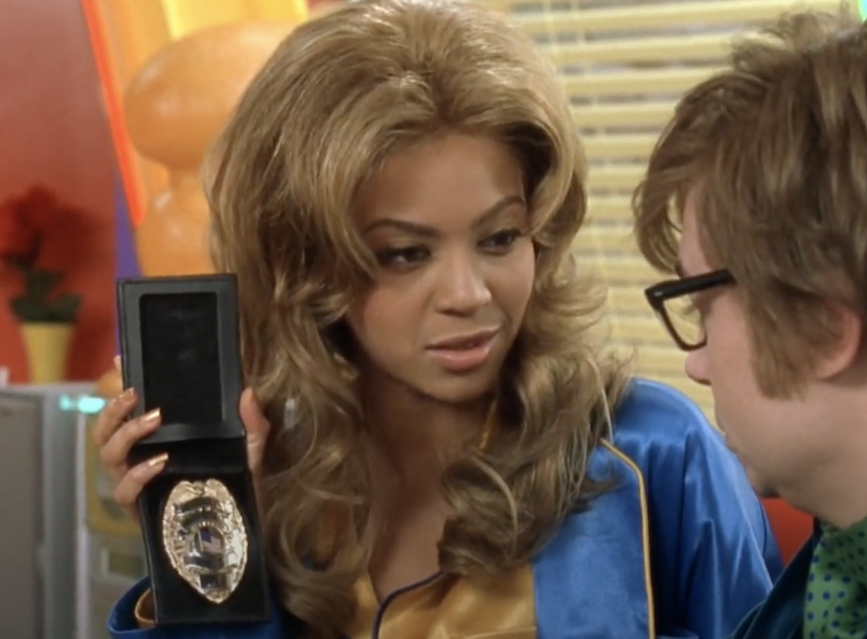 Foxxy holding up her detective badge to Austin in his house