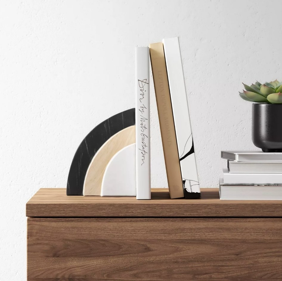 Black, white and wooden bookend holding books