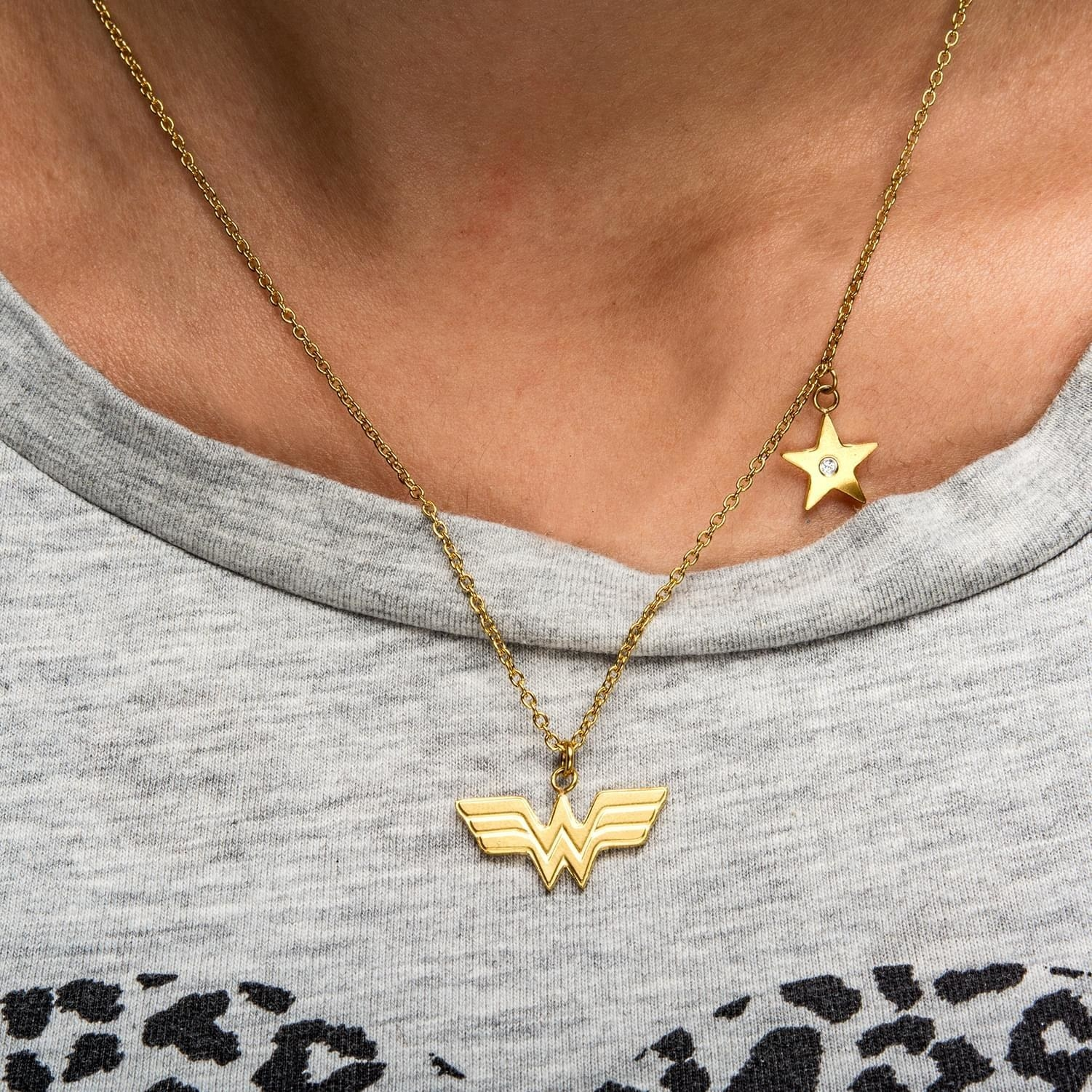 The delicate gold pendant necklace with a Wonder Woman logo charm and star charm with rhinestone in the center