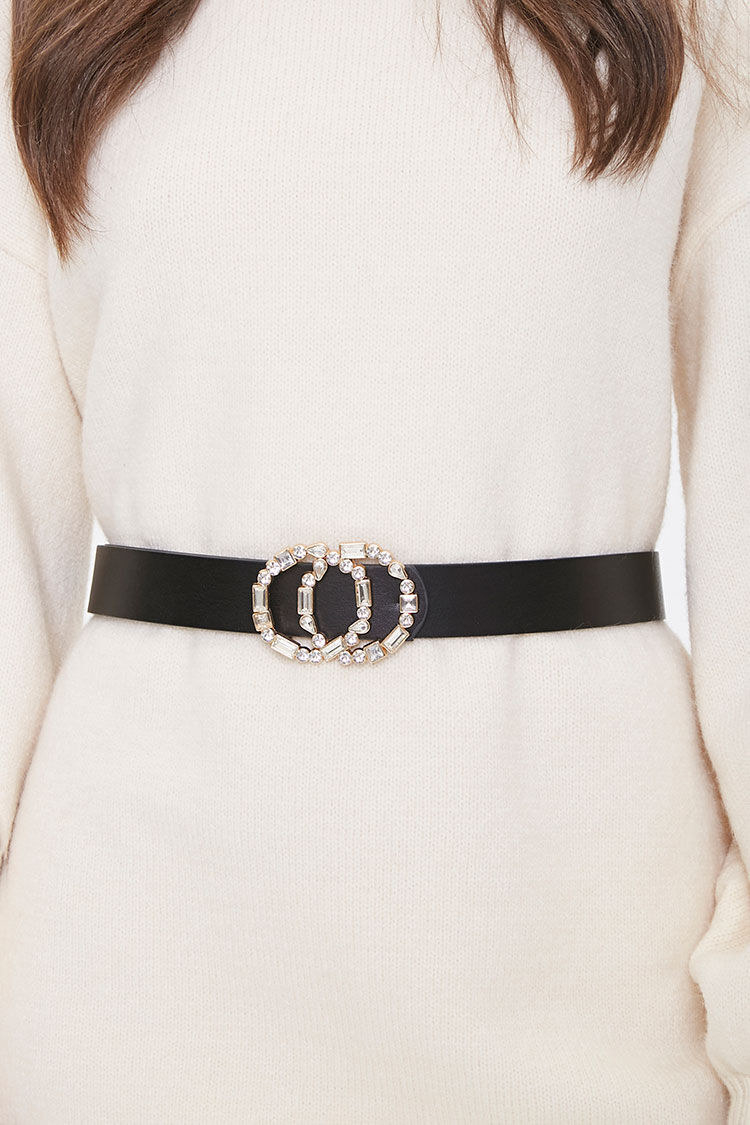 A model wearing the black mid-thickness belt with a clear jeweled buckle over a sweater dress