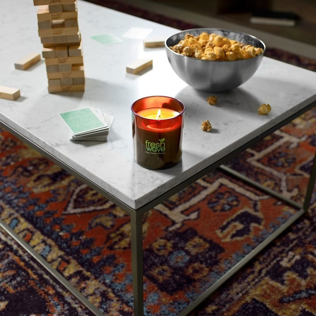 A candle perched on the edge of a coffee table