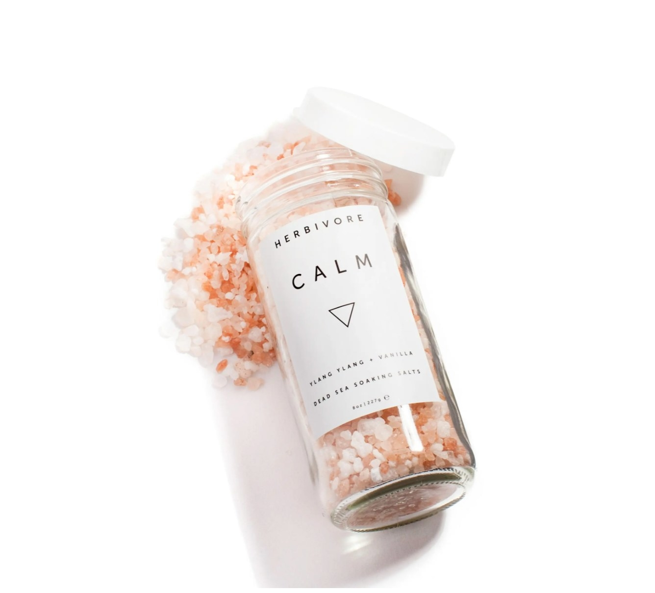 Clear bottle of pink bath salts with white cap