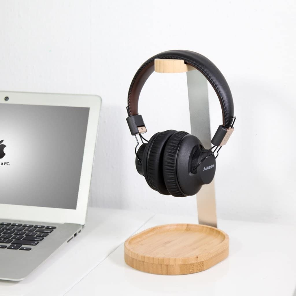 A wood and aluminum headphone stand holding large headphones on a desk