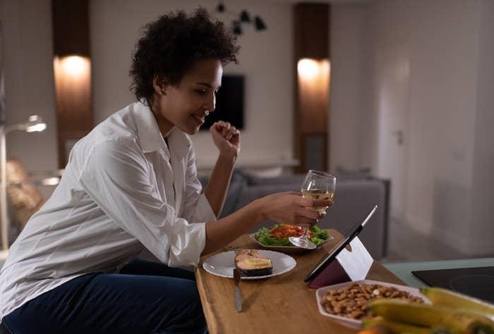 Mujer sostiene una copa de vino blanco en frente de una tableta. Hay comida en su mesa.