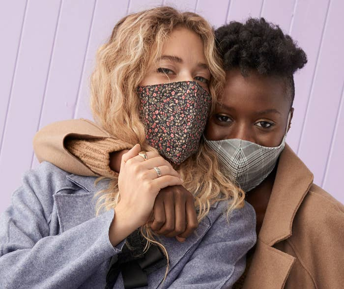 Two people wearing patterned masks