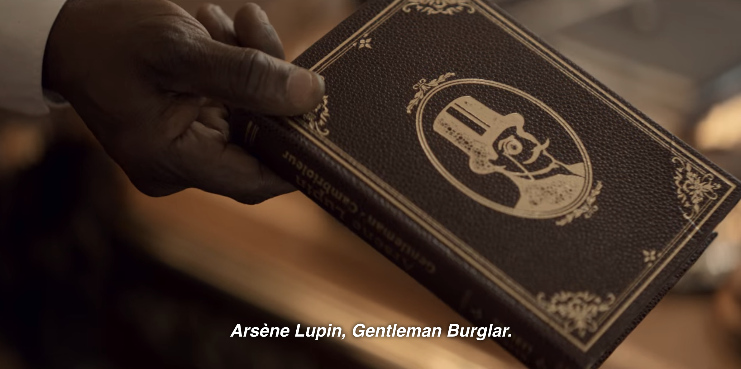A scene from the show where Babakar hands Assane the Lupin book