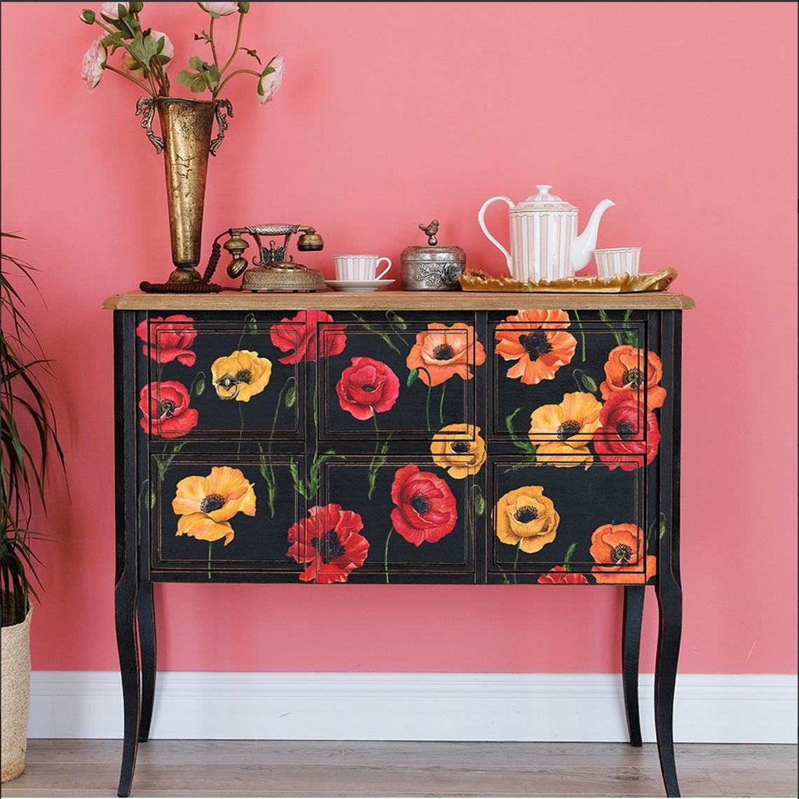 Black sideboard covered in red, yellow, and orange illustrated poppy flower decals