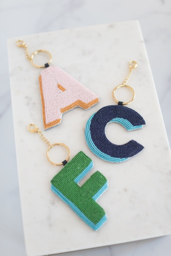 Three of the charms: a pink and orange A, a navy and blue C, and a blue and green F. All have a gold keyring and lobster clasp chain
