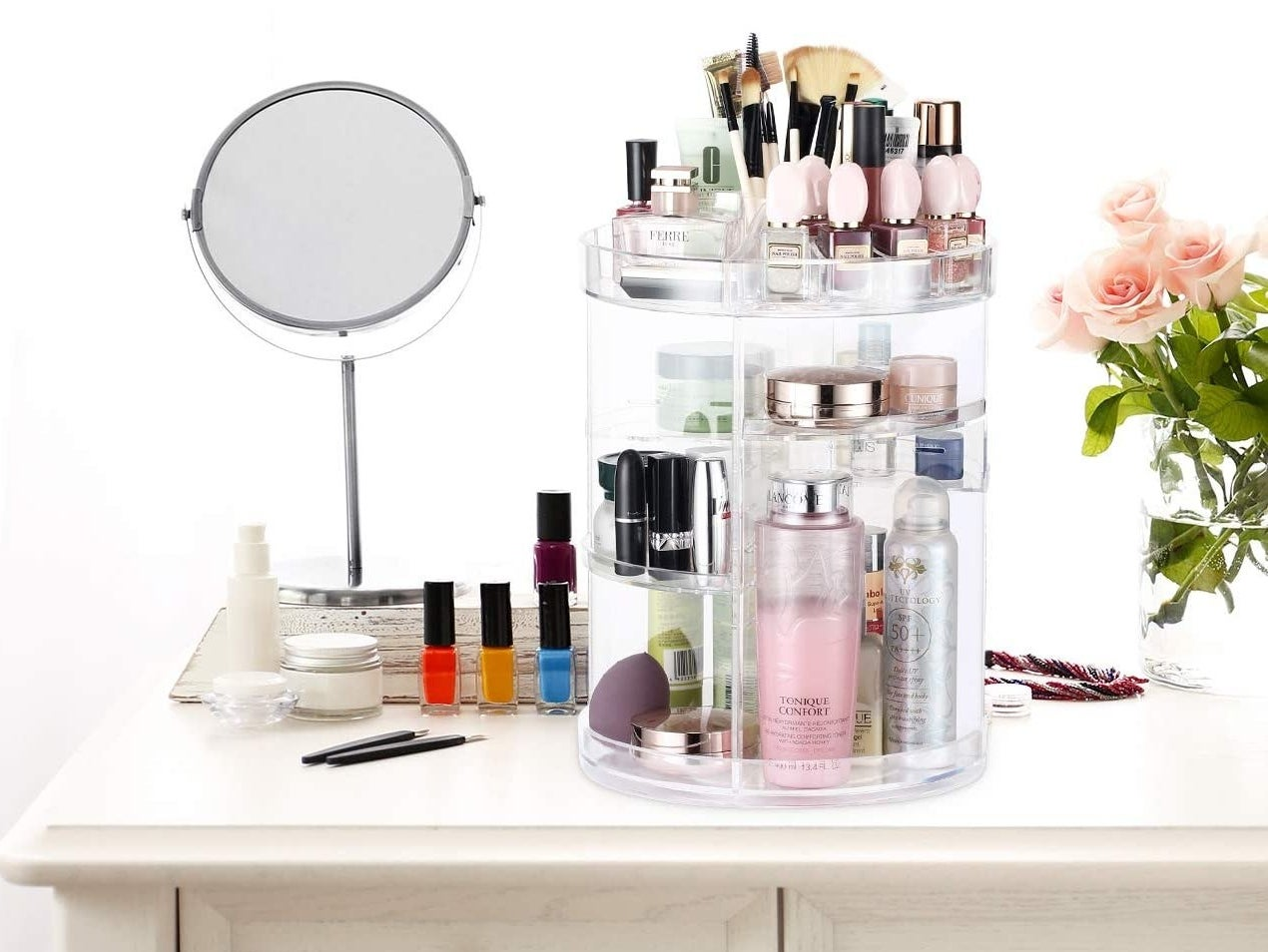 A clear rotating beauty organizer with several levels