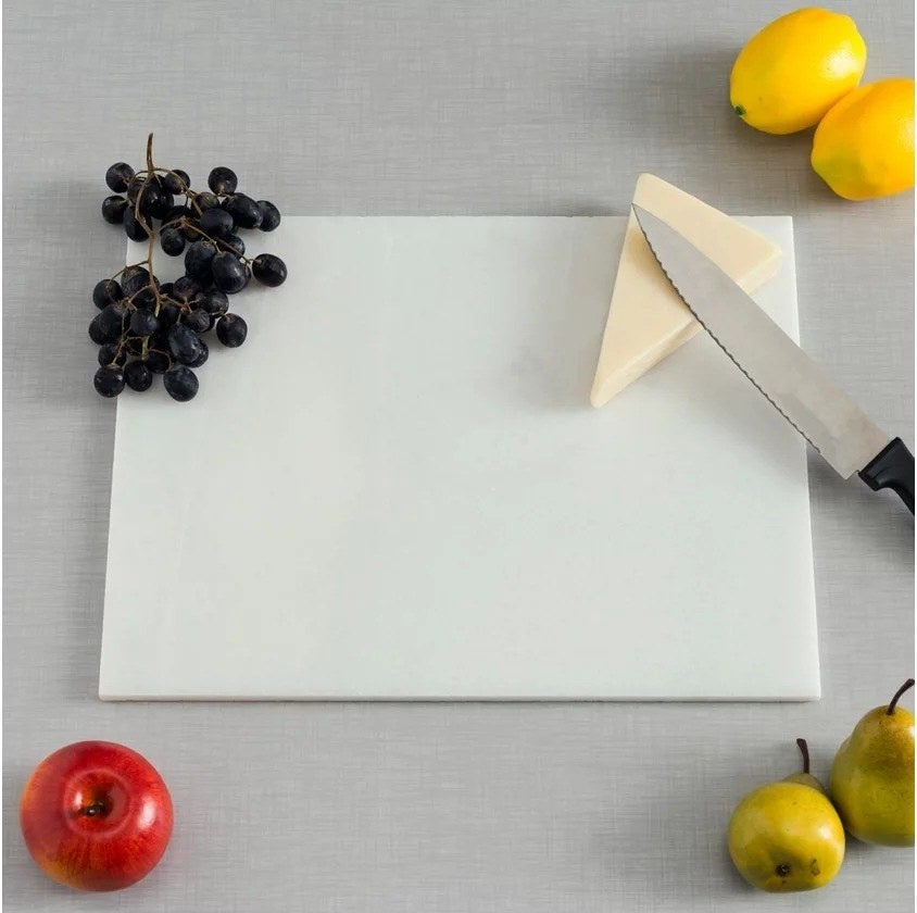 White Marble rectangular cutting board with a wedge of cheese and some grapes