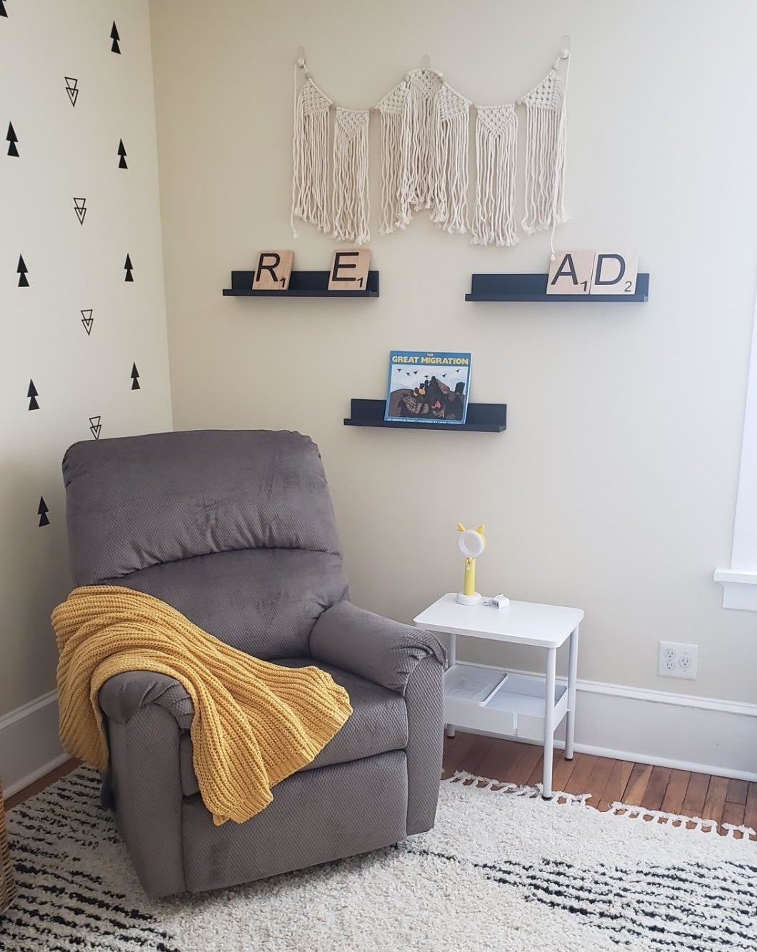 Reviewer's nursery with a recliner and three black ledge shelves on the wall behind, displaying books