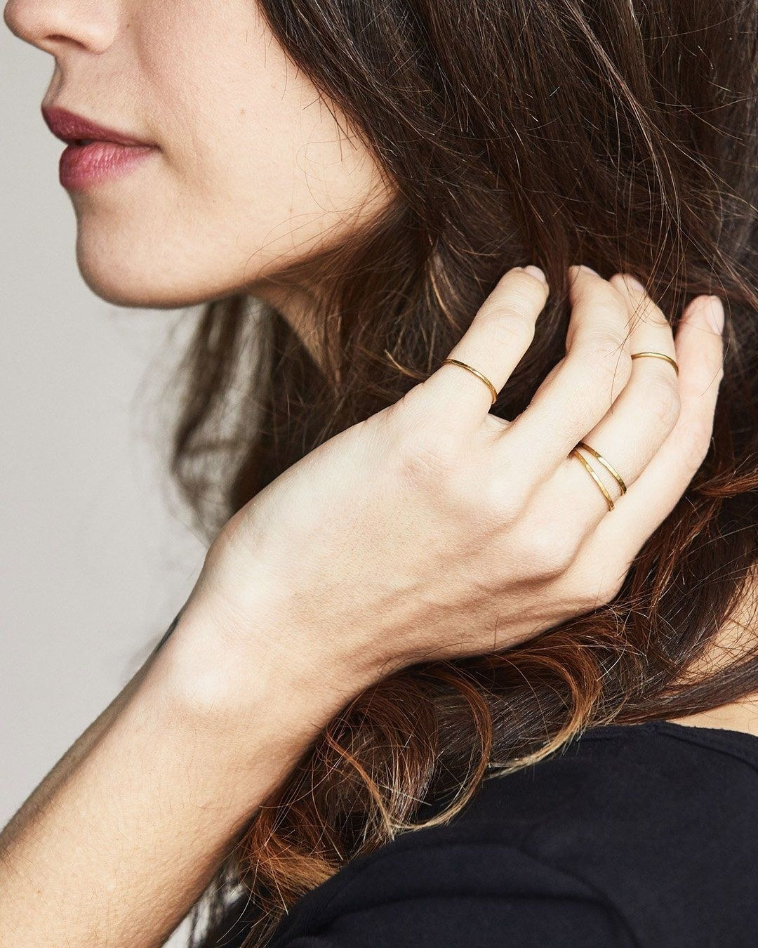 Model wearing several of the thin golden rings