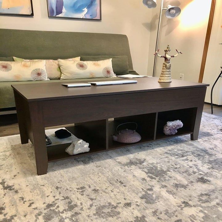 reviewer image of the coffee table in brown with three cubbies for storage across the bottom